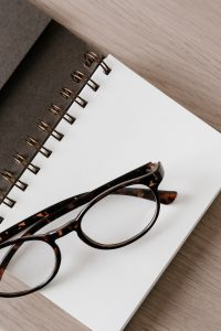 brown glasses on a paper notebook